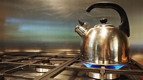 Stainless steel kettle is on cooking gas stove and boiling water. stock photo