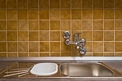 Stainless steel kitchen faucet and sink. Against ceramic tiled wall Royalty Free Stock Photography