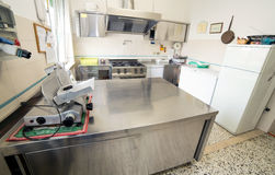 Stainless steel kitchen with gas stove and an industrial meat sl Royalty Free Stock Image