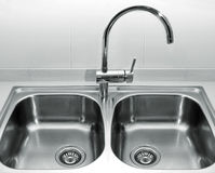 Stainless steel kitchen sink. A double bowl stainless steel kitchen sink on a white granite worktop Stock Image