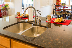Stainless Steel Kitchen Sink and Fixture. On Granite Countertop stock photo