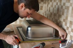 Stainless steel kitchen sink installation by man. Renovation of the kitchen. Stainless steel kitchen sink installation by a man. Renovation of the kitchen royalty free stock image