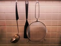 Stainless Steel Kitchen Utensils Hanging on the Wall Royalty Free Stock Images