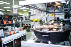 Stainless steel kitchenware set on shelves, shallow depth of field image
