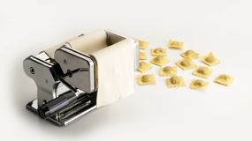 Stainless steel machine to flatten, fill and cut Italian pasta next to some ravioli samples. Seen on a white table stock image
