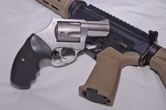 A stainless steel 357 magnum revolver with a black grip on top of a black and brown 223 caliber AR-15 rifle. With a white background royalty free stock image