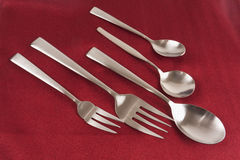 Stainless steel modern cutlery on red Stock Photos