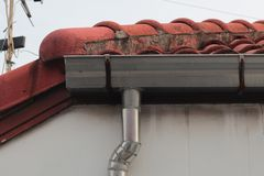 Stainless steel pipe gutter at corner roof with sky . stock photo