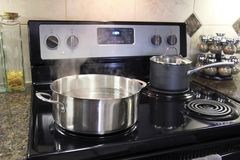 Stainless steel pot cooking on kitchen stove Royalty Free Stock Images