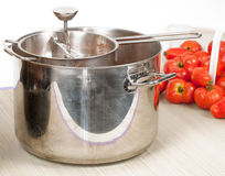 Stainless Steel Pot and Hand Mill. A front studio view of a stainless steel cooking pot and a stainless steel hand mill used for grinding fresh field tomatoes Stock Images