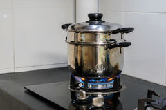 A stainless steel pot is placed on a gas stove. That is turned on for cooking in the kitchen royalty free stock photos
