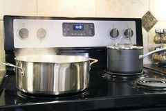 Stainless steel pots cooking on kitchen stove Stock Photo