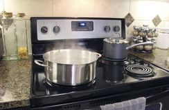 Stainless steel pots cooking on kitchen stove Stock Photos