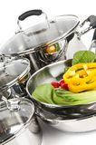 Stainless steel pots and pans with vegetables Royalty Free Stock Images