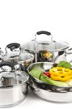 Stainless steel pots and pans with vegetables. Stainless steel pots and pans isolated on white background with vegetables Royalty Free Stock Image