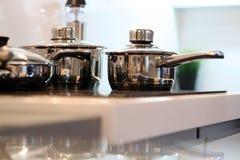 Stainless steel saucepans on modern kitchen.  Stock Image
