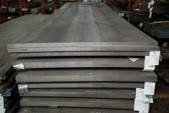 Stainless steel sheets deposited in stacks. Stainless steel bars deposited in stacks in a deposit Stock Images
