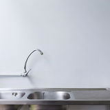 Stainless steel sink and faucet in white kitchen Royalty Free Stock Photo