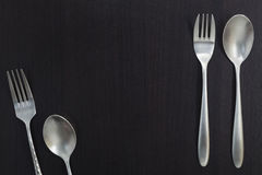 Stainless steel spoon on black wood background. Stock Photo
