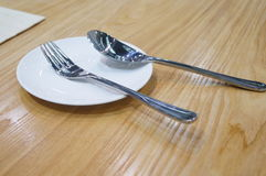 Stainless steel spoon. In the white plate Stock Images