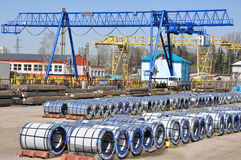 Stainless steel storage yard. With two shear legs cranes, polymer rolls and tubes in packs Royalty Free Stock Image