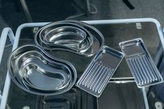 Stainless steel surgical Instrument trays of various sizes. On glass table stock photography