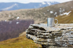 Stainless steel thermo mug on a flat stone within tne mountains. Stainless steel thermo mug on a flat stone, like on a table, with spring mountains behind it Royalty Free Stock Photography