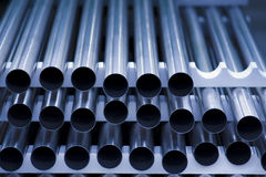 Stainless steel tubes stacked. Stack of steel tubes stacked on a factory floor with very limited depth of field Stock Image