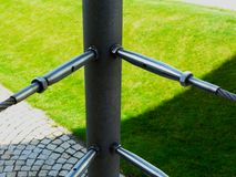 stainless steel turnbuckle and steel wire cable railing with blurry green yellow grass background. stock images