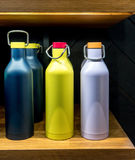 Stainless steel vacuum water bottle with twist off lid for cold. Beverages on wooden shelf. Easy carry design for travel or sports Stock Images