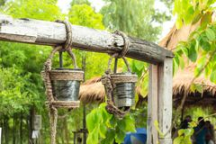 Stainless steel water tanks that hung on a log for a bath. royalty free stock photo