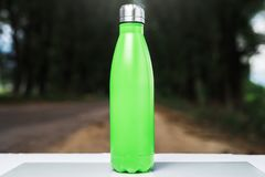 Stainless thermos water bottle on white table, outdoor. Light green color. royalty free stock photos