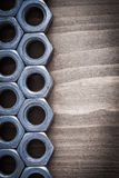 Stainless threaded construction nuts on vintage wooden board con Royalty Free Stock Image