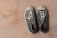 stainly zapatos viejos en la tierra sucia del cemento Foto de archivo