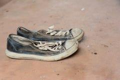 stainly zapatos viejos en la tierra sucia del cemento Fotos de archivo libres de regalías