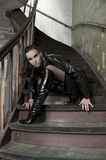On the stair. Fashion shot of a brunette model with black leather coat and boots posing in old stairs Royalty Free Stock Photography