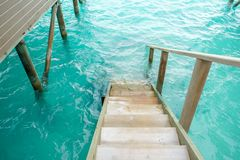 Stair down to crystal clear ocean from water villa private balcony, Maldive. S royalty free stock images