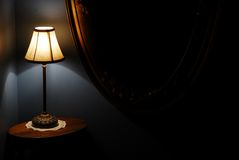 Stair Landing Night Lamp. View of stair landing night lamp on table, with antique oval wall mirror Royalty Free Stock Image