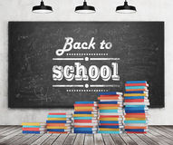 A stair is made of colourful books. Back to school is written down the black chalkboard. Concrete wall, wooden floor and three black ceiling lights royalty free stock image