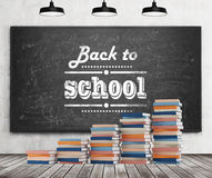 A stair is made of colourful books. Back to school is written down the black chalkboard. Concrete wall, wooden floor and three bla. Ck ceiling lights royalty free stock images