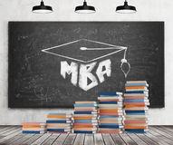 A stair is made of colourful books. A graduation hat is drawn on the black chalkboard. MBA concept. Stock Photography