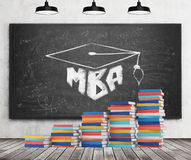 A stair is made of colourful books. A graduation hat is drawn on the black chalkboard. MBA concept. Concrete wall, wooden floor an Stock Images