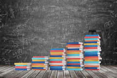 A stair is made of colourful books. A graduation hat is on the final step. Black chalk board with math formulas on the background. Wooden floor stock image