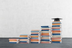 A stair is made of colourful books. A graduation hat is on the final step. Stock Image