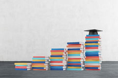 A stair is made of colourful books. A graduation hat is on the final step. Concrete wall and wooden floor royalty free stock image