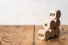 A stair symbolized by cubes and the slogan: step by step stock photos