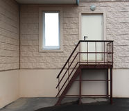 Stair to backdoor against patterned wall and mock up windows.  stock photo
