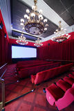 Staircase, baffle and seats in cinema hall. Staircase, baffle and red seats in cinema hall with big lusters Royalty Free Stock Image