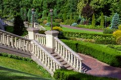 The staircase with balustrades railing down to the path for walking. The staircase with balustrades railing down to the path for walking through the park with royalty free stock photo