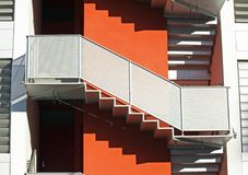 Staircase of a building orange and the shadows of the steps Stock Photos